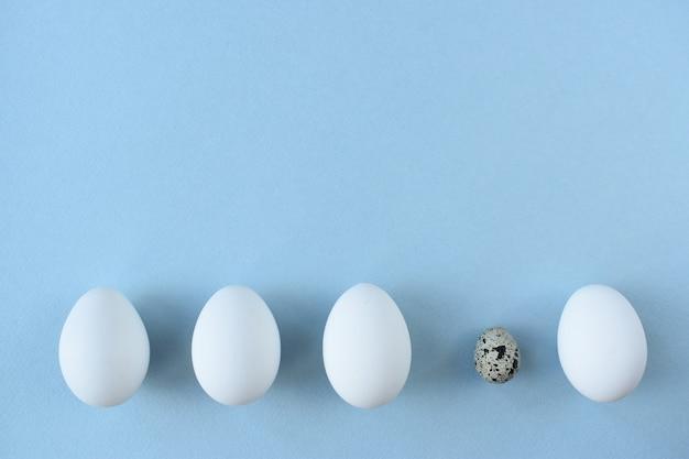 Vier weiße eier und eine wachtel auf blauem grund