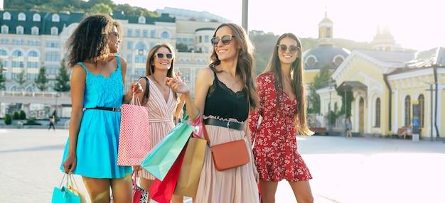 Vier wunderschöne frauen in sommerlichen outfits posieren auf der straße in der innenstadt, lächeln vor freude und zeigen ihre einkäufe in die kamera