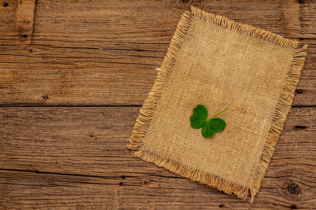 Vierblättriges kleeblatt, frische pflanze auf sackleinen. viel glück symbol, st.patrick's day konzept