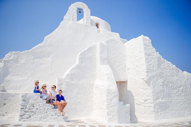 Vierköpfige familie auf der treppe von paraportiani-kirche auf mykonos-insel, in griechenland