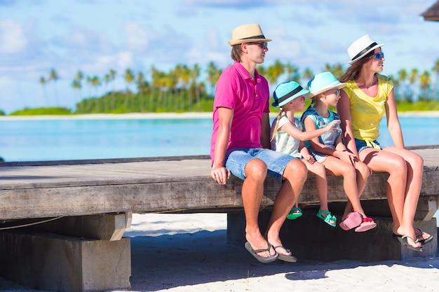 Vierköpfige familie auf hölzerner anlegestelle bei malediven