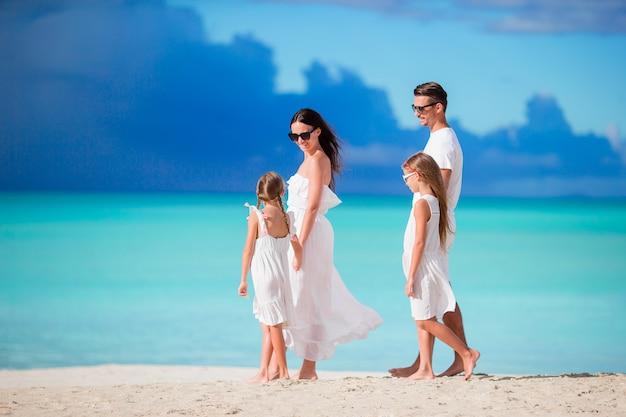 Vierköpfige familie, die auf weißen strand geht
