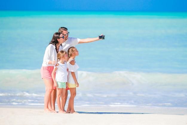Vierköpfige familie, die ein selfie foto auf dem strand macht. familienurlaub