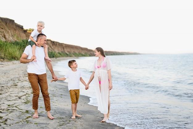 Vierköpfige familie, die entlang die küste geht. eltern und zwei söhne. glückliche freundliche familie
