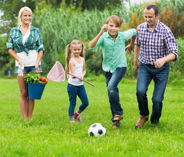 Vierköpfige familie, die fußball spielt und spaß hat