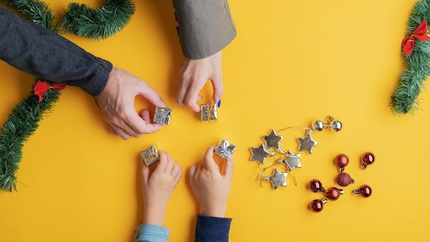 Vierköpfige familie, die mini-geschenke auf gelbem raum mit verstreuten feiertagsverzierungen platziert.