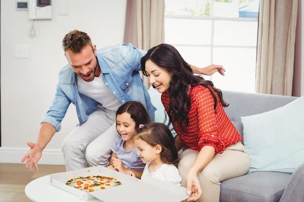 Vierköpfige familie, die pizza auf tabelle betrachtet
