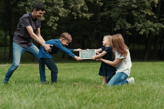 Vierköpfige familie, die spaß beim spielen im park hat