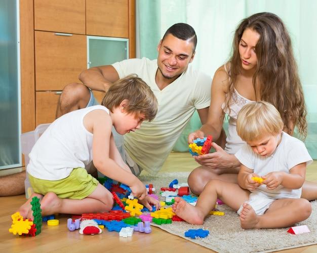 Vierköpfige familie zu hause mit spielwaren