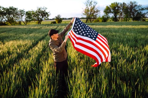 Vierter juli. patriotischer mann mit der amerikanischen nationalflagge im feld. junger mann, der stolz eine amerikanische flagge schwenkt. tag der unabhängigkeit.