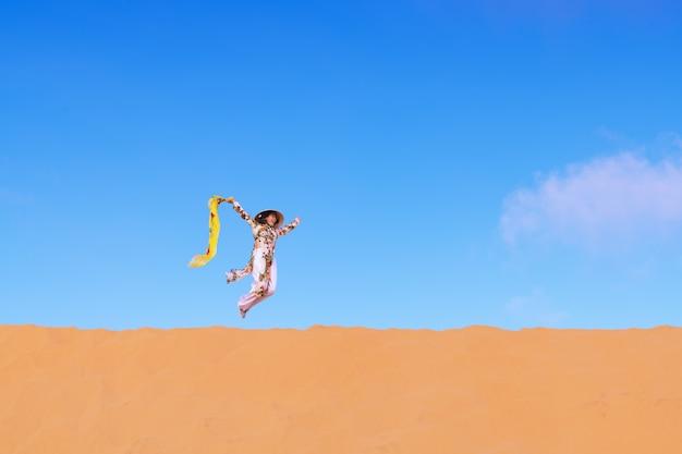 Vietnam-frau, die das traditionelle springen der ao dai-kultur auf die wüste bei muine in vietnam trägt