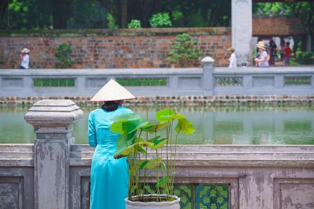 Vietnam-frau, die einen strohhut und ein blaues kleid ao dai trägt, die neben dem teich im touristenattraktionszentrum im literatur-tempel hanoi vietnam stehen.