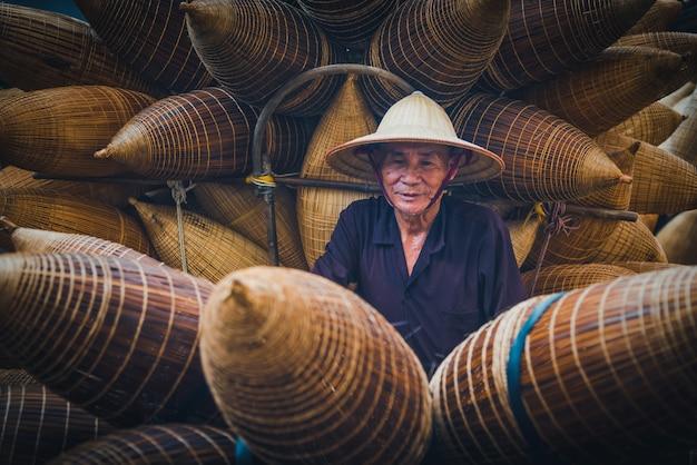 Vietnamesische fischer machen am morgen in thu sy village, vietnam, korbwaren für angelausrüstung.