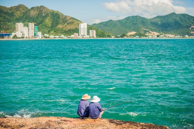 Vietnamesische fischer sitzen am rand einer klippe und fischen.