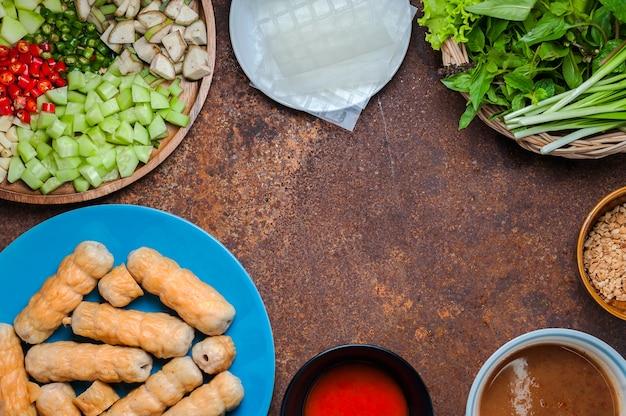 Vietnamesische fleischklöschen-verpackungen (nam neung) dienten mit gemüse, wurst auf rustikaler tabelle.