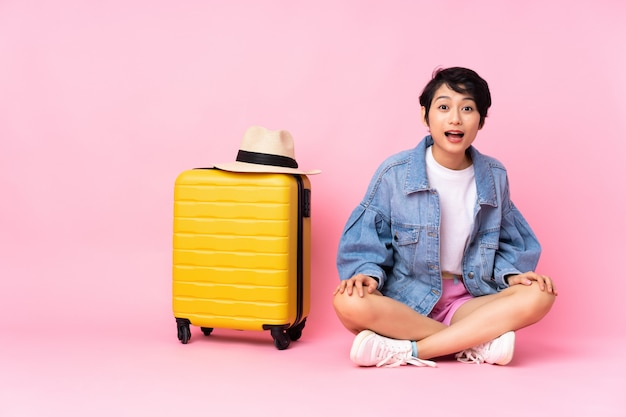 Vietnamesische frau des jungen reisenden mit koffer, der auf dem boden über rosa wand mit überraschtem gesichtsausdruck sitzt