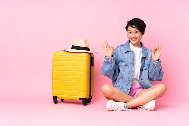 Vietnamesische frau des jungen reisenden mit koffer, der auf dem boden über rosa wand sitzt und ein ok-zeichen mit den fingern zeigt