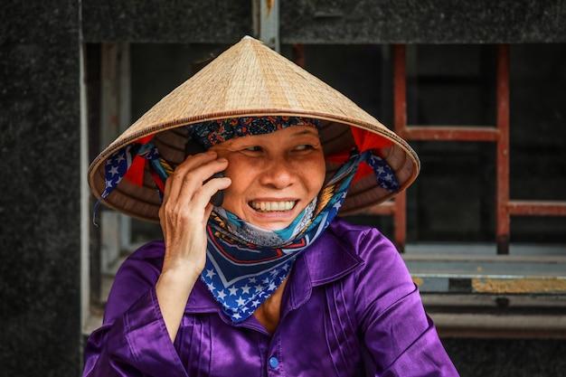 Vietnamesische frau, die am moblie telefon auf straße in hanoi, vietnam nimmt