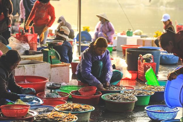 Vietnamesische frau, die meeresfrüchte von den großen schüsseln an einem straßenrandmarkt in hoi an, quang nam province verkauft