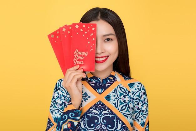 Vietnamesische frau traditionelles festivalkostüm ao da mit roten geldtaschen. tet urlaub. mondneujahr.