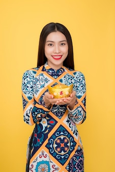 Vietnamesische frau traditionelles festivalkostüm ao dai. tet urlaub. mondneujahr. text bedeutet reich.