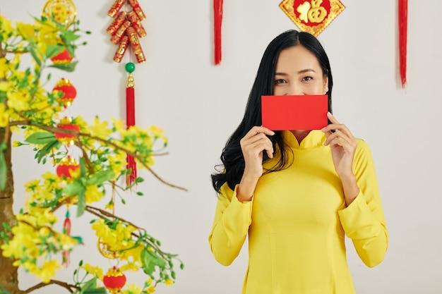 Vietnamesische frau zeigt roten umschlag