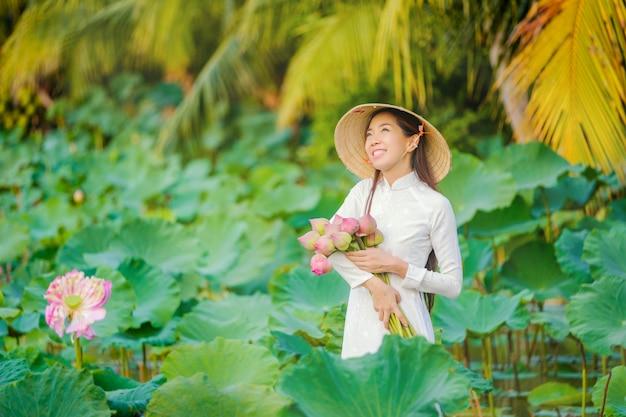 Vietnamesische frauen sammeln den lotos bei sonnenuntergang.