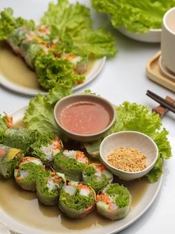Vietnamesische frühlingsrollen mit dip und gemüse auf esstisch