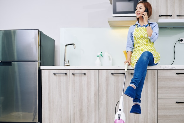 Vietnamesische hausfrau mit staubsauger in der hand, die auf küchentheke sitzt und mit freund am telefon spricht