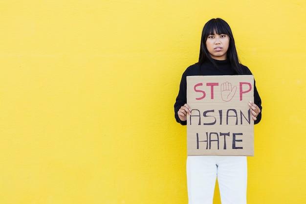 Vietnamesische junge frau, die für gleiche rechte protestiert, während sie während der kampagne zum stopp der asiatischen hassbekämpfung gegen eine gelbe wand steht