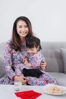 Vietnamesische mutter und tochter in ao dai tracht, feiern neues jahr zu hause. tet urlaub.