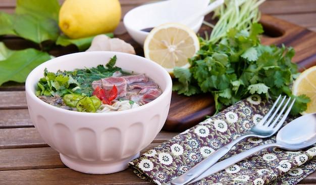 Vietnamesische nudelsuppe mit brühe, linguinenförmigen reisnudeln, koriander und rindfleisch