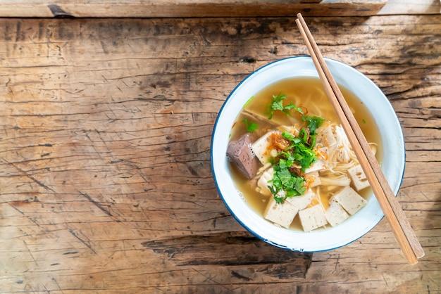 Vietnamesische reisnudelsuppe mit schweinefleisch und hühnchen auf holztisch Premium Fotos