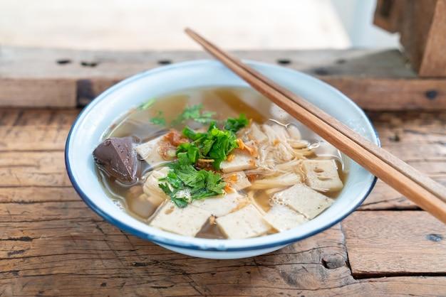 Vietnamesische reisnudelsuppe mit schweinefleisch und huhn auf holztisch