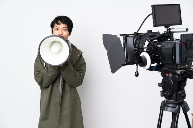 Vietnamesische reporterin, die ein mikrofon hält und nachrichten meldet, die durch ein megaphon schreien