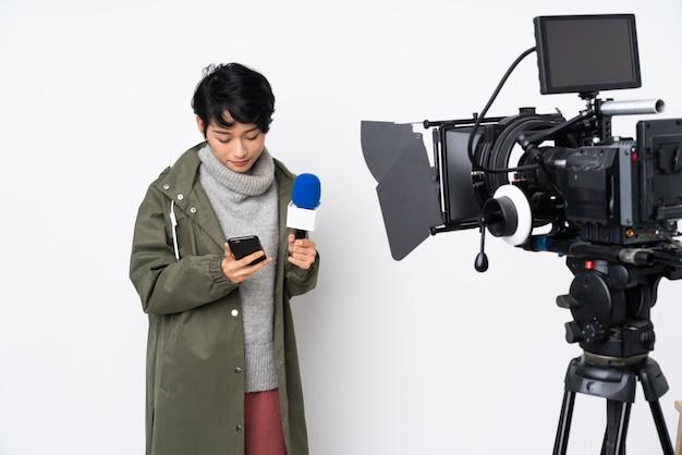 Vietnamesische reporterin, die ein mikrofon hält und nachrichten meldet, die eine nachricht mit dem handy senden