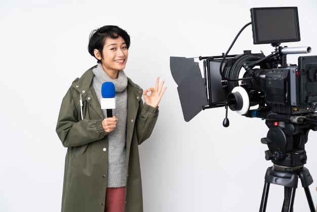 Vietnamesische reporterin hält ein mikrofon und meldet nachrichten, die ein ok-zeichen mit den fingern zeigen
