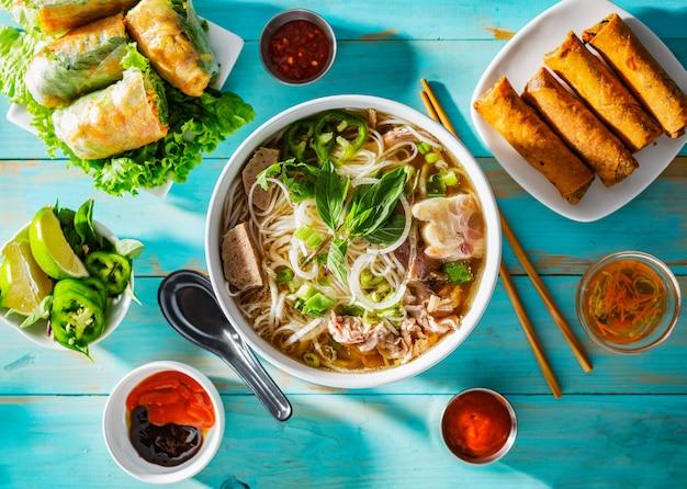 Vietnamesische rindfleisch pho bo suppe in schüssel auf tischplatte mit frühlingsrollen und vorspeisen