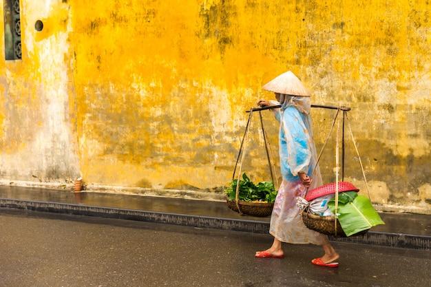 Vietnamesischer frauenstraßenverkäufer in hoi ein vietnam in der alten stadt hoian