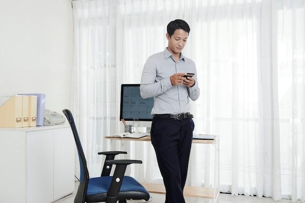 Vietnamesischer geschäftsmann, der in seinem hauptbüro steht und textnachricht auf seinem telefon liest