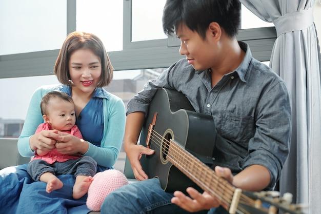 Vietnamesischer junger mann, der gitarre spielt und für seine kleine tochter singt
