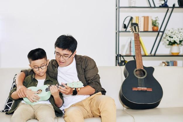 Vietnamesischer mann, der seinen talentierten jugendlichen sohn unterrichtet, der zu hause ukulele spielt