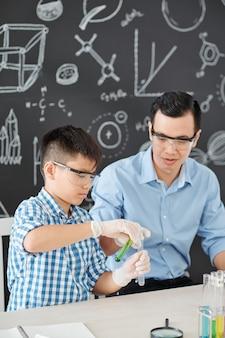 Vietnamesischer schüler in einer schutzbrille, die reagenzien unter kontrolle des chemielehrers mischt