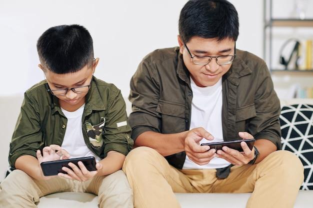 Vietnamesischer vater und sohn in gläsern sitzen auf sofa und spielen auf smartphones