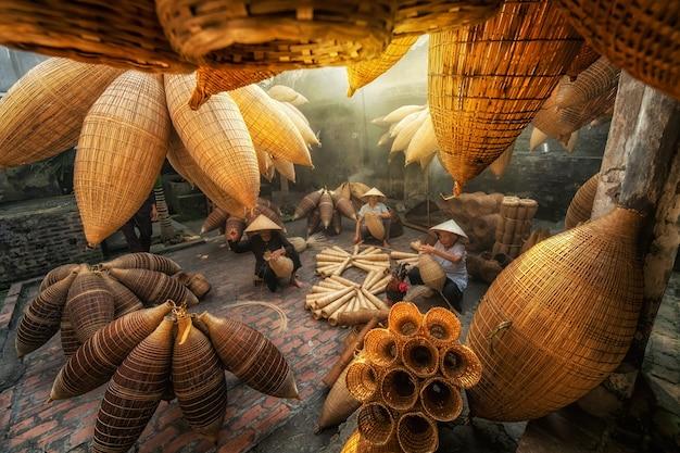 Vietnamesischer weiblicher handwerker, der die traditionelle bambusfischfalle am alten haus bildet