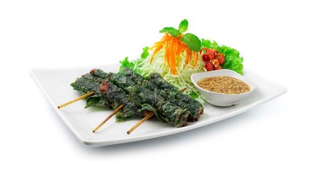 Vietnamesisches essen gebratenes schweinefleisch, eingewickelt in wild betal leaf serviert süße sauce mischung erdnuss gehackte fusion food vietnamesische art