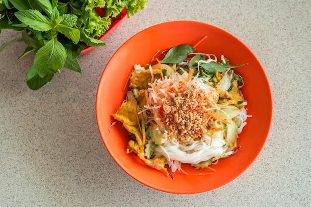 Vietnamesisches essen, reisnudeln mit gemüse und schweinefleisch.