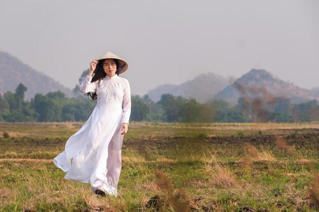 Vietnamesisches mädchen im weißen kleid, das einen hut trägt, geht