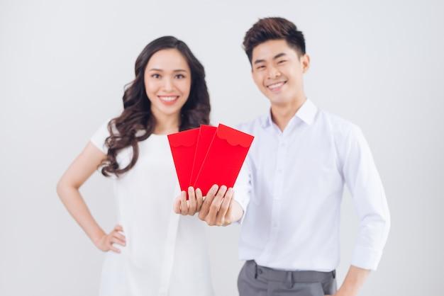 Vietnamesisches paar, das rote glückliche geldumschläge austauscht. tet urlaub.