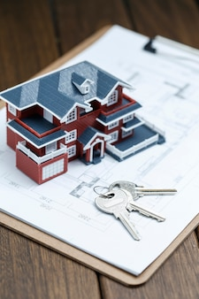 Villa haus-modell, schlüssel und zeichnung auf retro-desktop (immobilien-verkauf-konzept)